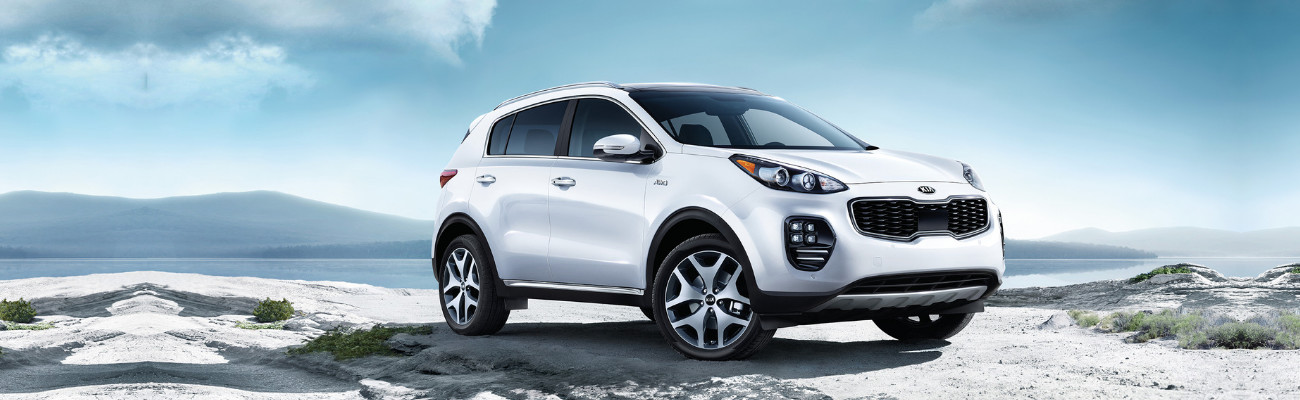 Front passenger side view of a white 2019 Kia Sportage SUV sitting at the top of a cliff overlooking a hazy mountain range