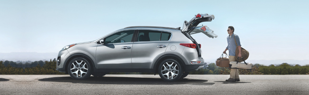 Driver side look at a silver 2019 Kia Sportage with the driver loading baggage into the back cargo space on the side of a cliff overlooking a forest
