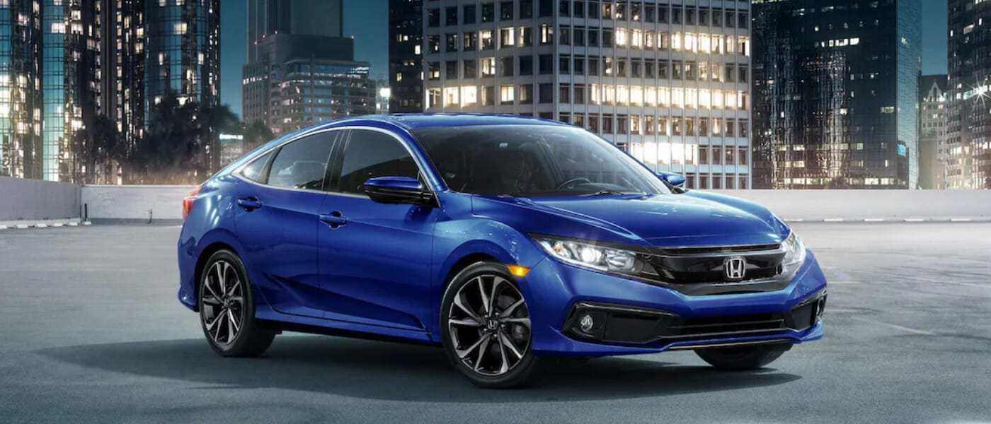 Blue 2019 Honda Civic on top of city parking garage at night
