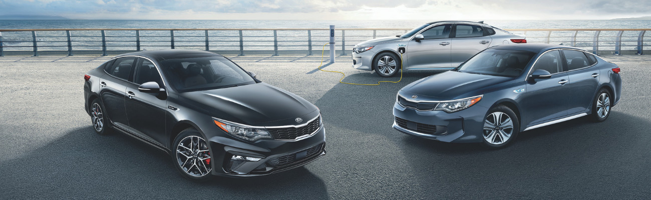 Zoomed out view of a 2019 Kia Optima, 2019 Kia Optima Hybrid, & 2019 Kia Optima Hybrid Plug-In parked on a concrete ledge overlooking a body of water under the rising sun
