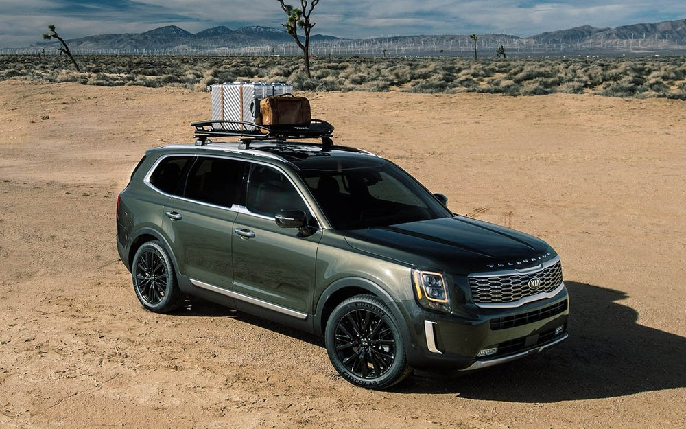 Green Telluride with a roof rack and luggage in the desert