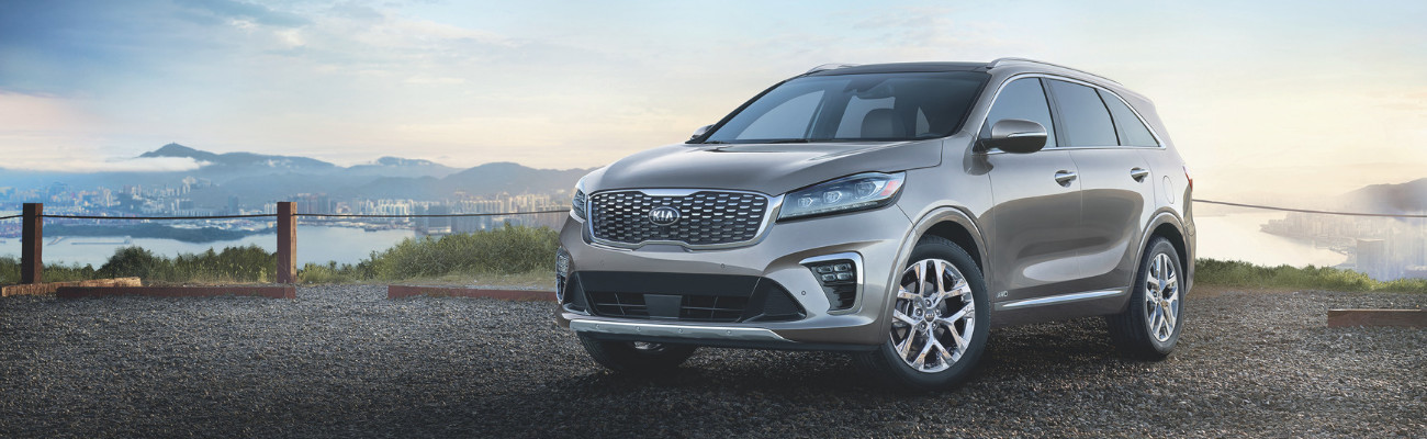 Driver side view of a 2019 Kia Sorento parked on a rocky cliff roped off on the edge overlooking a city at sunset