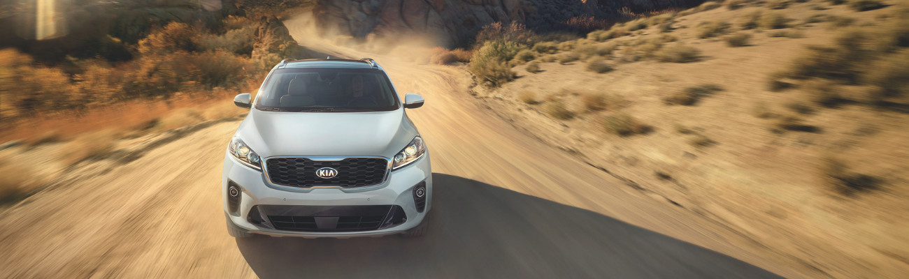 Front angle of a 2019 Kia Sorento driving down a dirt path in a hot desert scene with dust clouds behind the SUV