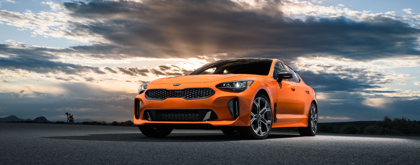 A deep orange 2020 Kia Stinger in front of a epic sunset