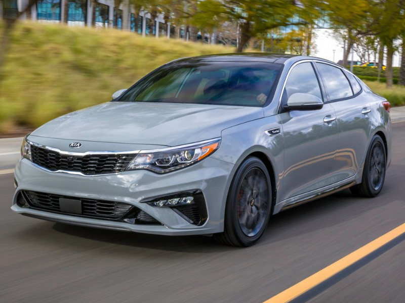 Front exterior view of a 2019 Kia Optima speeding down an open highway