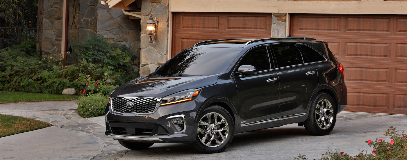 One of the most popular Kia SUVs for sale, a black Sorento in front of an upscale PA house