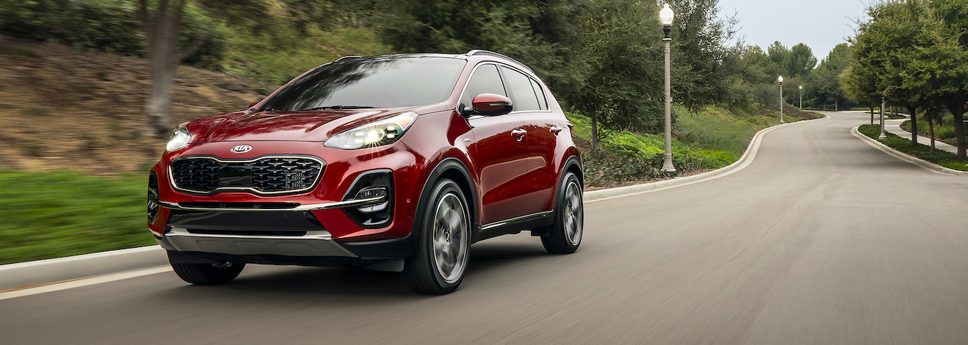 A red 2020 Kia Sportage travels a suburban PA road
