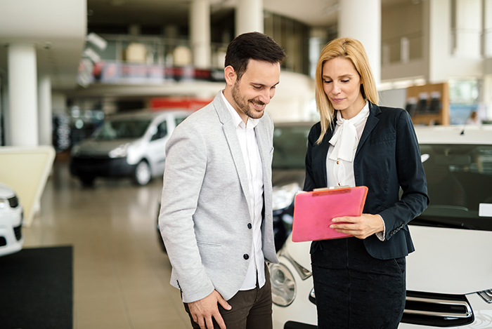 when to trade in your vehicle at Superior Toyota in Erie | Sale associate showing man financial information