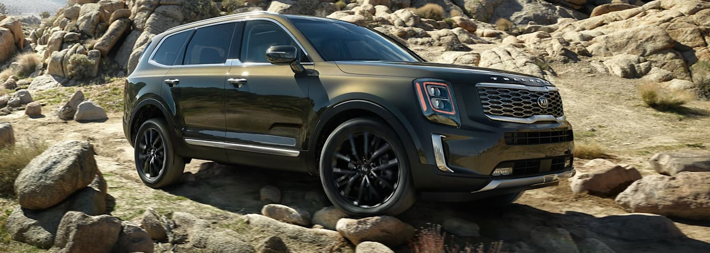 A green 2020 Kia Telluride is parked on a rocky trail.