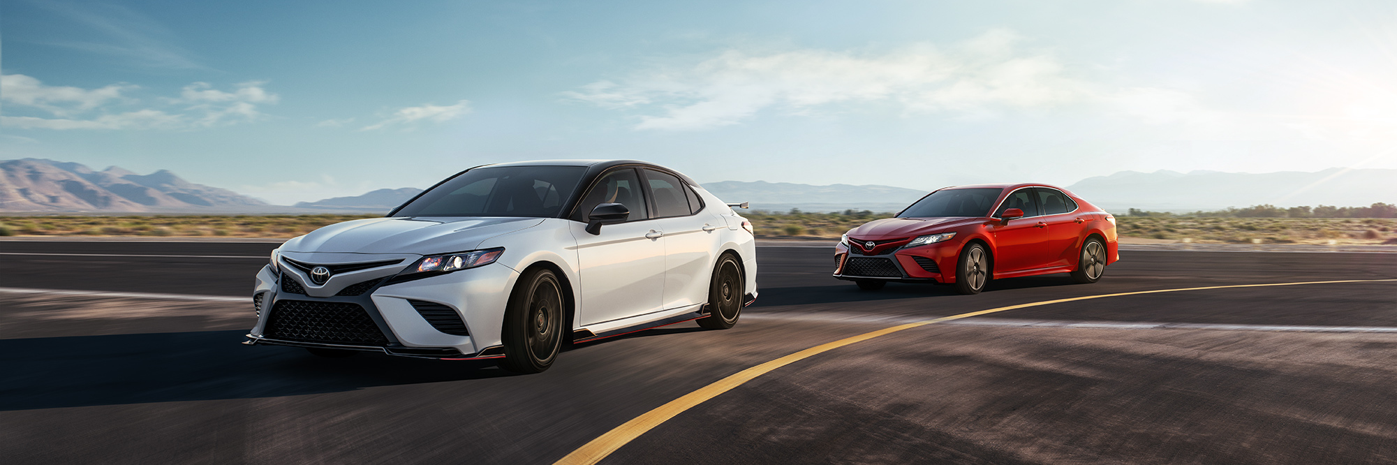 Model Features of the 2020 Toyota Camry at Tri County Toyota | White and red 2020 Camry Running on road
