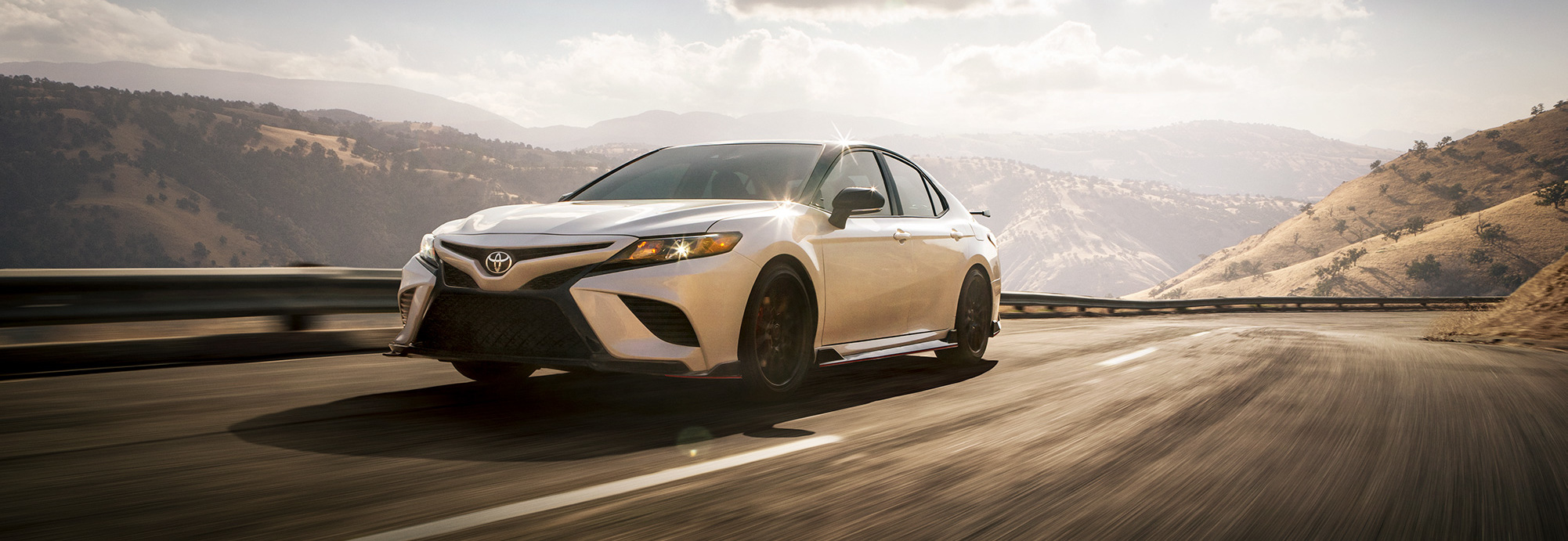 Model Features of the 2020 Toyota Camry at Tri County Toyota | White 2020 Camry TRD running on road