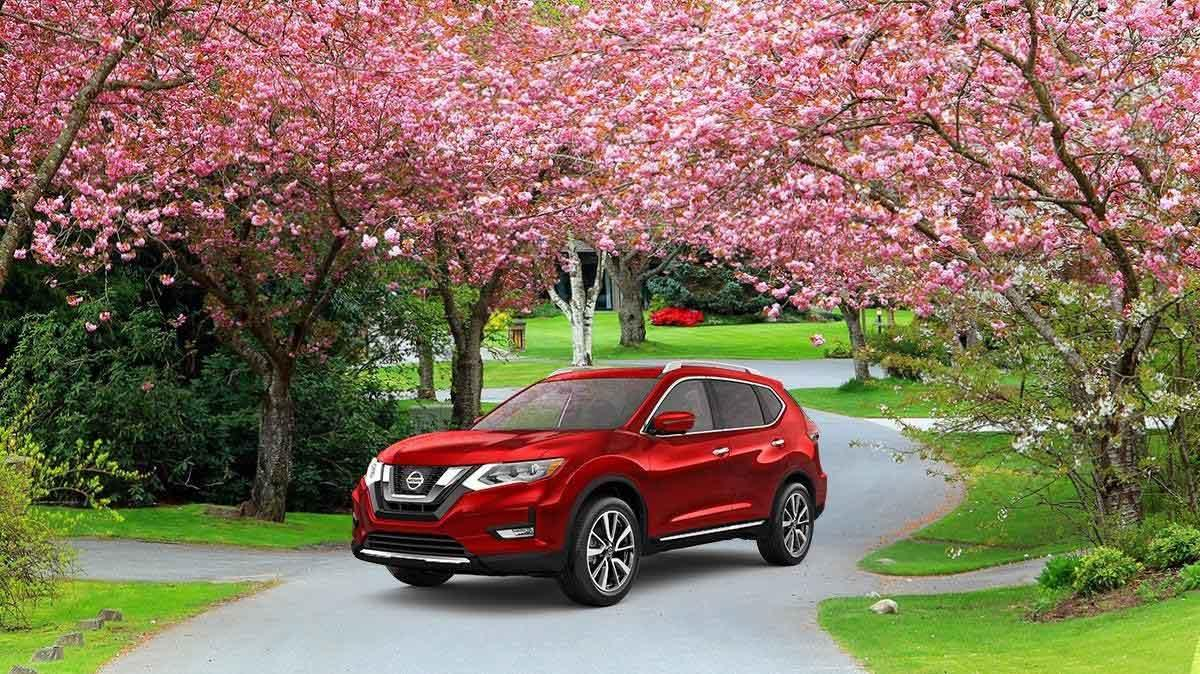 A red Nissan Rogue on a driveway lined with blossoming trees.