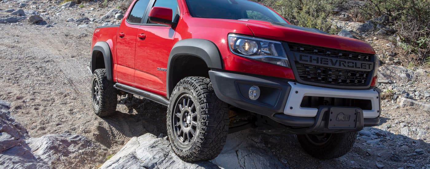 A red 2019 Chevy Colorado ZR2 Bison is off-roading on a rocky trail.