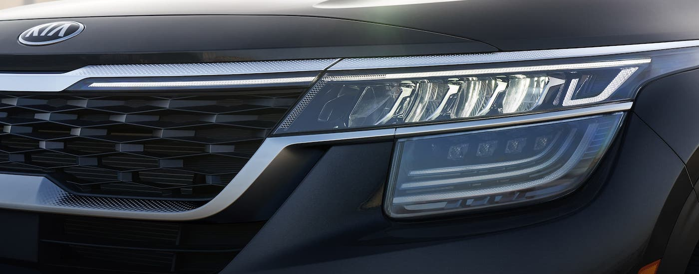 A closeup of the grille and headlight on a black 2021 Kia Seltos is shown.