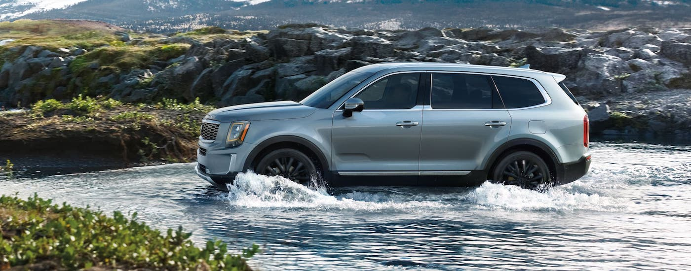 A profile view of a silver 2020 Kia Telluride from Quakertown, PA, that is driving through a river.