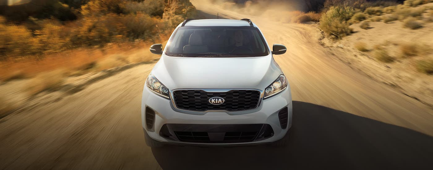 A white 2020 Kia Sorento is shown from the front driving on a desert road.