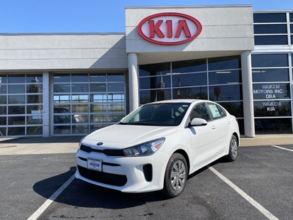 Picture of a white Kia Rio parked in front of a gray building with a red Kia logo on it