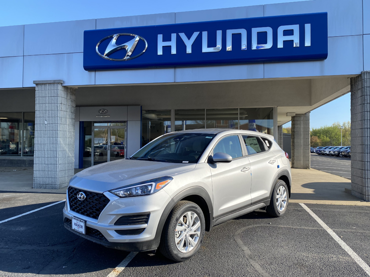 Picture of Gray Hyundai Tucson SUV parked in front of a gray and blue building with the Hyundai logo behind it