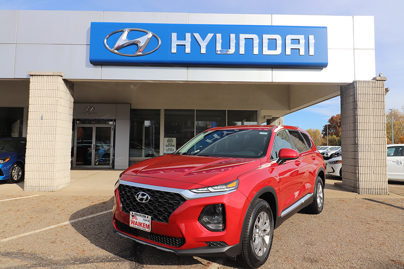 Picture of a red Santa Fe SUV parked in front of a gray and blue building with Hyundai logo