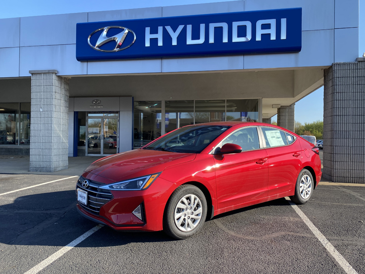 Picture of red Hyundai Elantra parked in front of a gray and blue building with the Hyundai logo