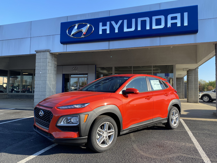 Picture of a red Hyundai Kona SUV parked in front of a gray and blue building with the Hyundai logo behind it