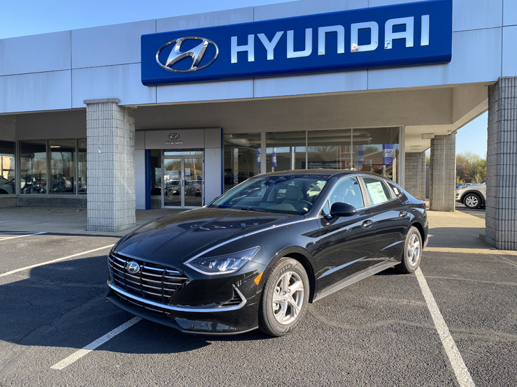Picture of a black Hyundai Sonata sedan parked in front of a gray and blue building with the Hyundai logo behind it