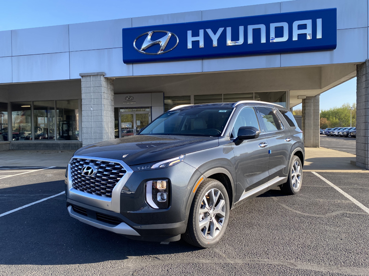 Picture of a gray Hyundai Palisade SUV parked behind a gray and blue building with the Hyundai logo behind it.