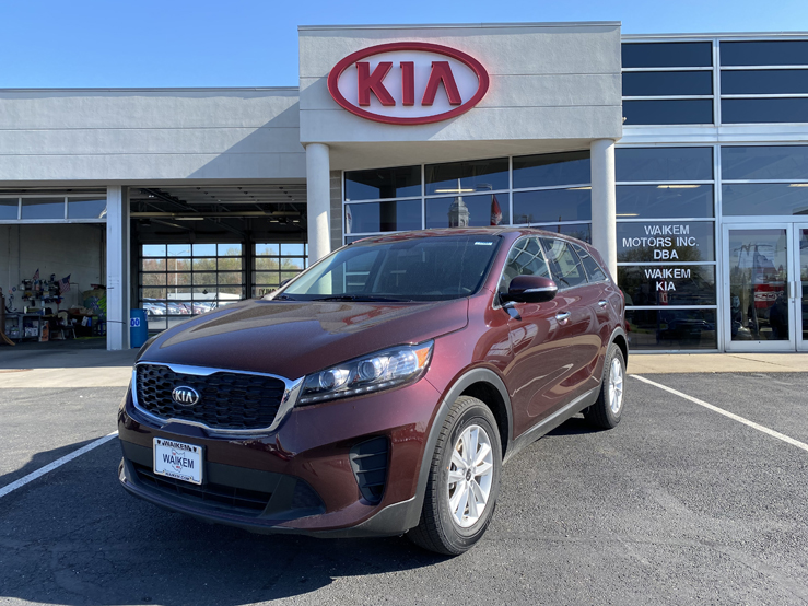 Picture of a red Kia Sorento SUV parked in front of a gray building with a red Kia logo behind it.