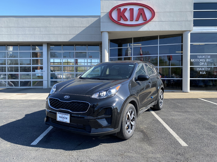 Picture of a black Kia Sportage parked in front of a gray building with a red Kia logo on it.