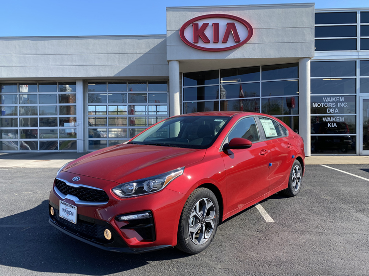 Picture of a red Kia Forte car sedan parked in front of a gray building with a red Kia logo on it
