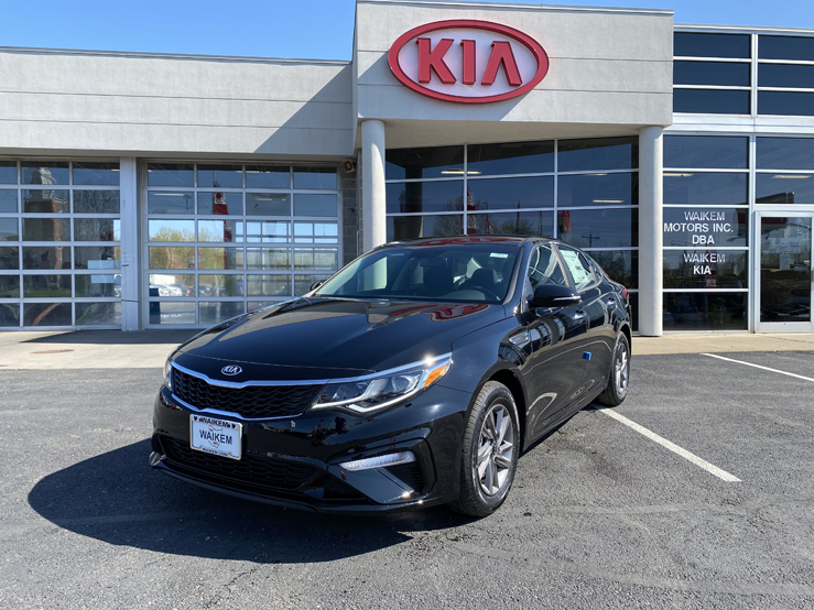 Picture of a black Kia Optima car sedan parked behind a gray building with a red Kia logo on it