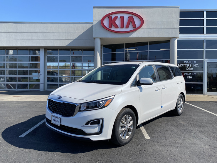 Picture of a white Kia Sedona minivan parked in front of a gray building with a red Kia logo on it