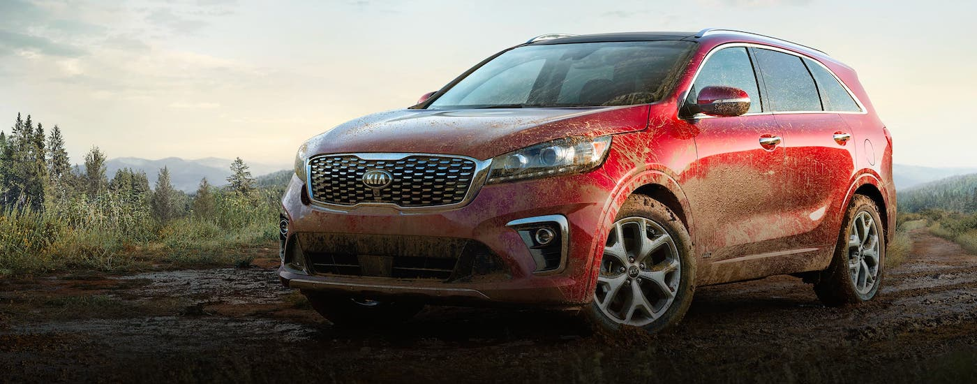 A red 2020 Kia Sorento is parked in the woods near Allentown, PA, and covered in mud.