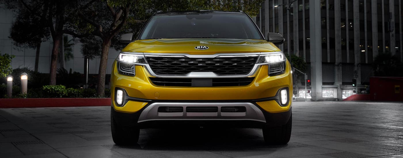 A yellow 2021 Kia Seltos is parked in a city and shown from the front at dusk.