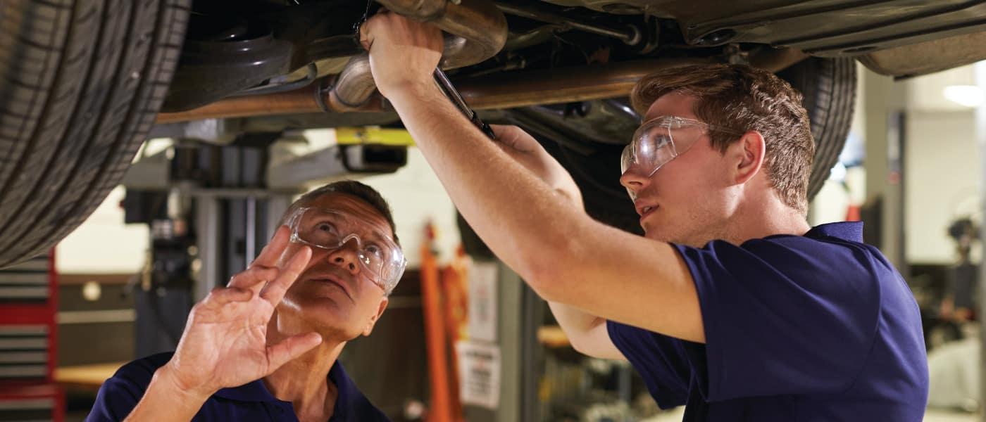 mechanics-working-on-bottom-of-car