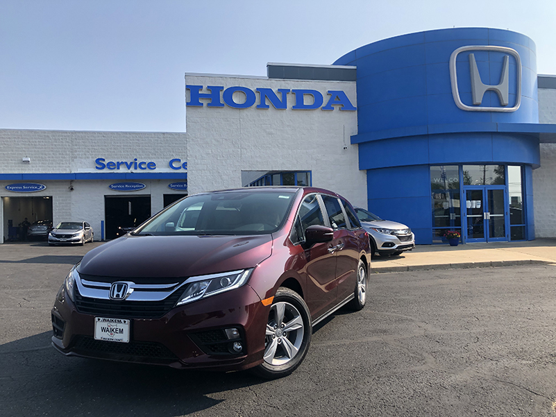 Picture of a red Honda Odyssey parked in front of a gray and blue Honda Dealership