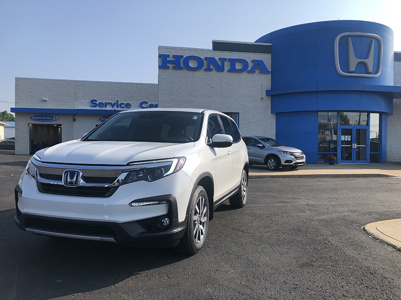 Picture of a white Honda Pilot parked in front of a gray and blue Honda dealership