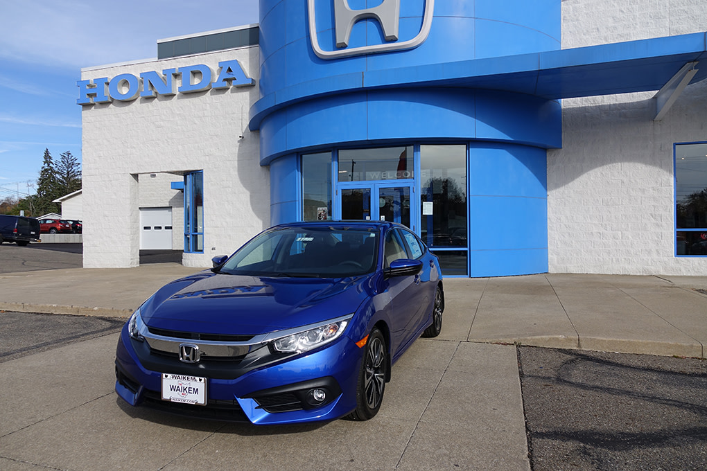 A picture of a blue Honda Civic sedan in front of Waikem Honda in Massillon, OH
