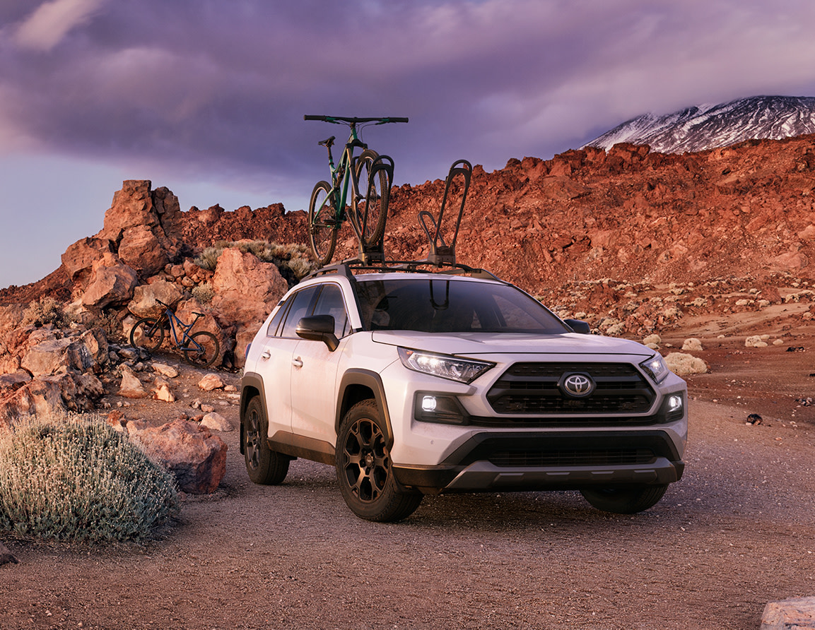 Compare the 2020 Toyota RAV4 vs. the Honda CR-V crossovers at Tri County Toyota | white 2020 rav4 parked in a mountain terrian