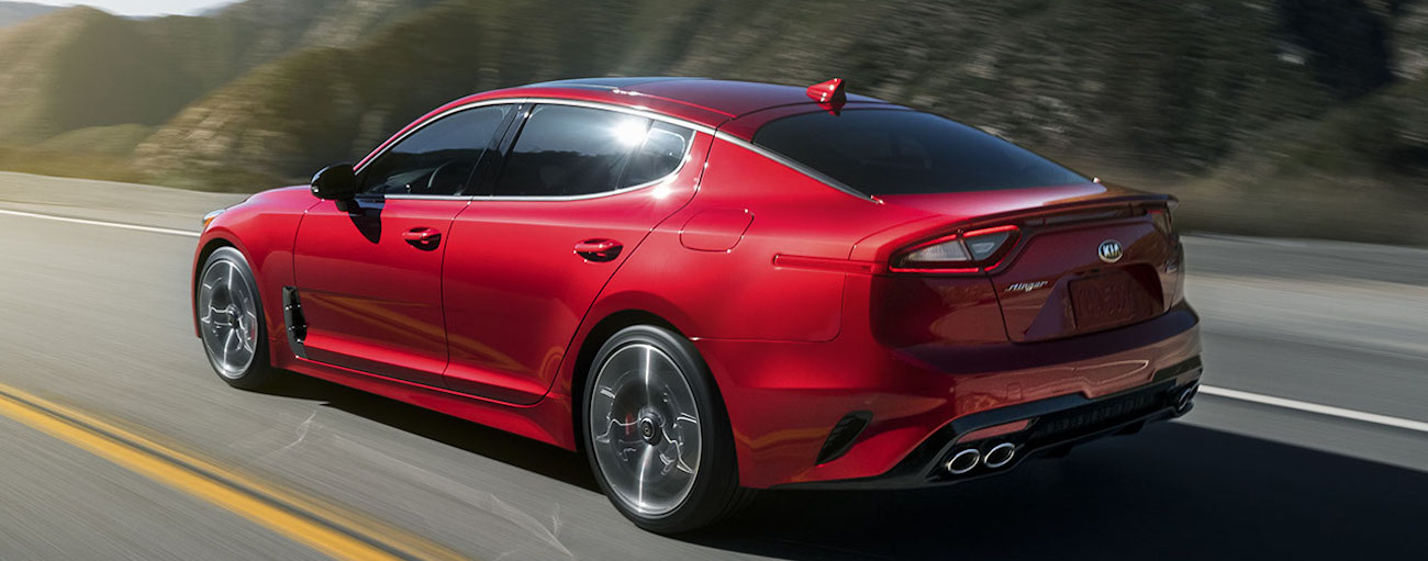 A red 2019 Kia Stinger cruises an open highway on a test drive from a Kia dealership near you