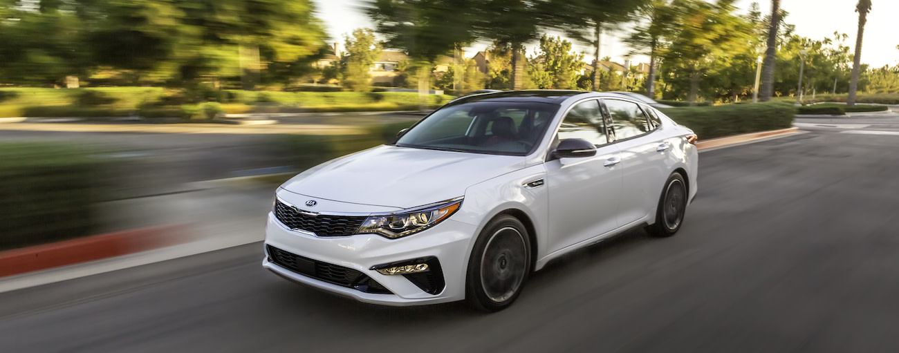 A white 2019 Kia Optima on a test drive from a local dealer in Allentown PA