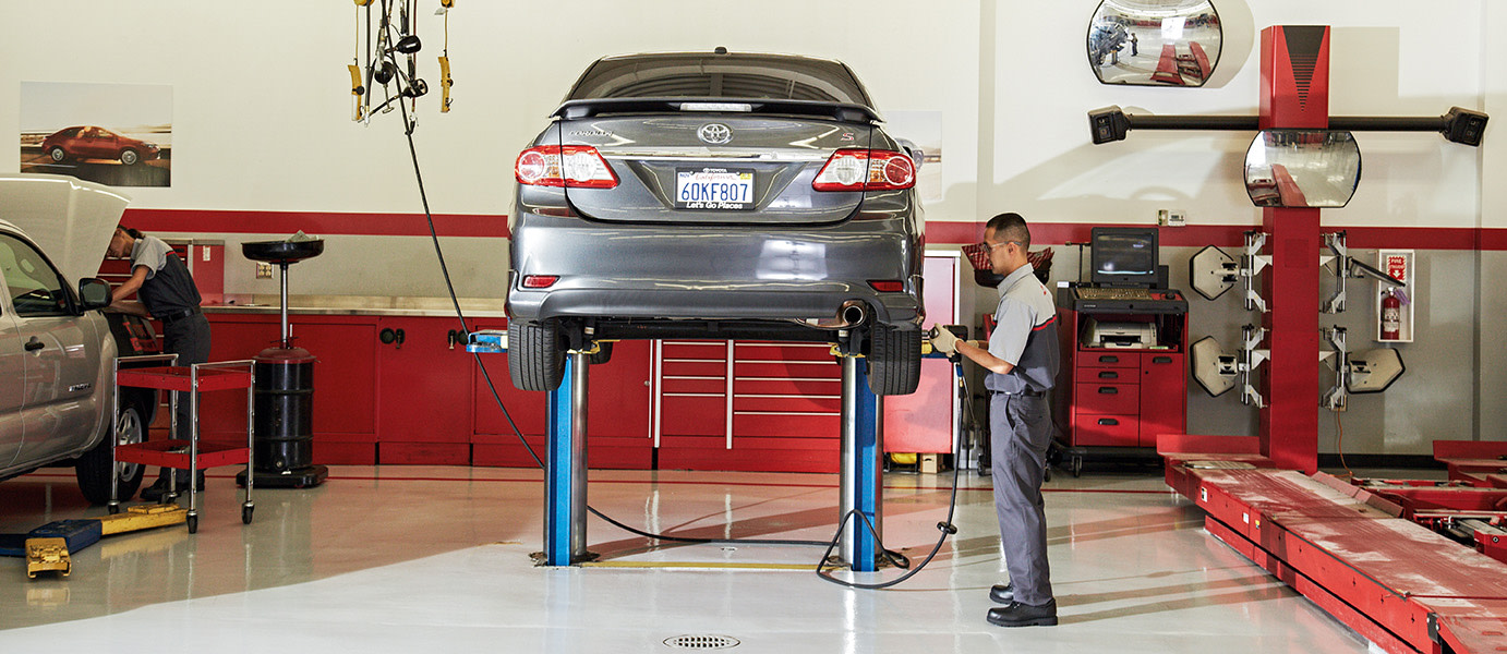 Team Toyota of Glen Mills is a Toyota Dealership near Kennett Square PA   2020 Toyota Service Technician changing tires on gray Toyota sedan in Toyota Service Center