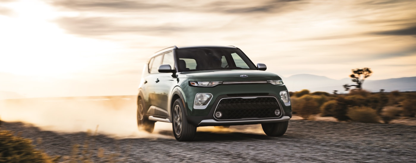 A green 2020 Kia Soul rips up a dirt road at sunset