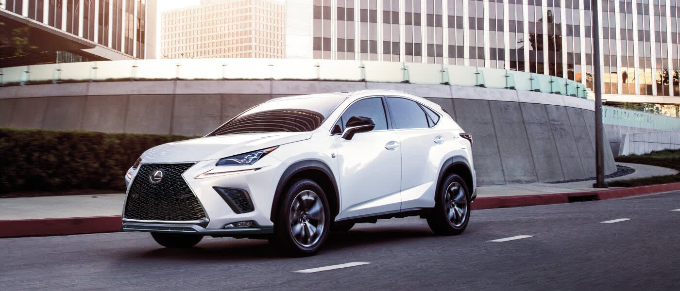 A white 2020 Lexus NX 300 driving down a city street