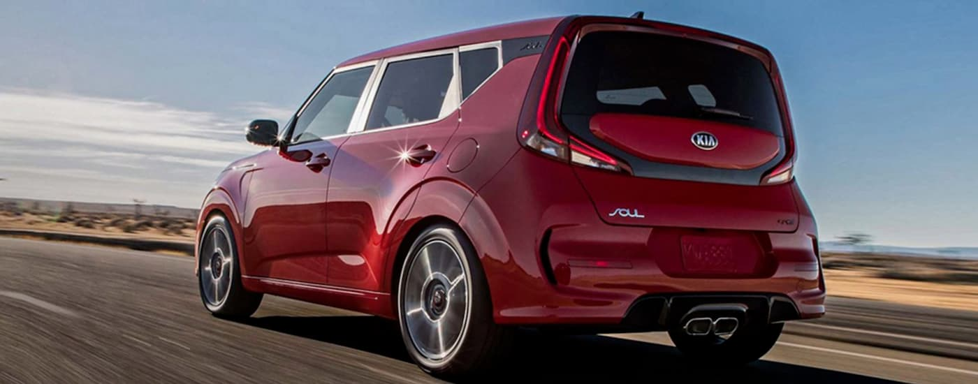 A red 2020 Kia Soul, popular among Kia SUVs for sale, is driving on a desert road.
