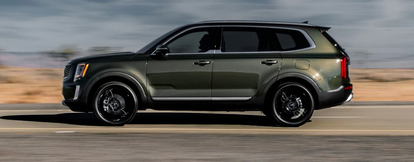 A green 2020 Kia Telluride is shown driving from the side.