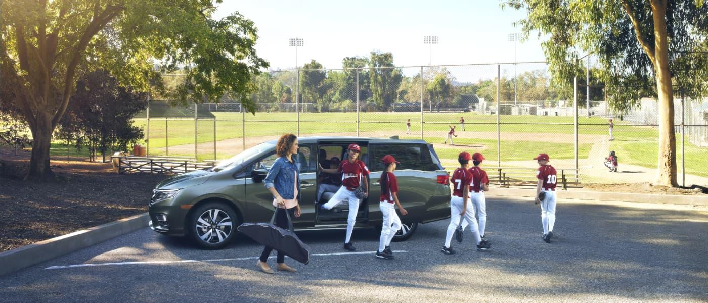Honda Odyssey parked at a kids baseball game