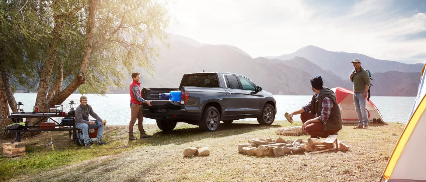 2020 Honda Ridgeline parked outside with a family camping