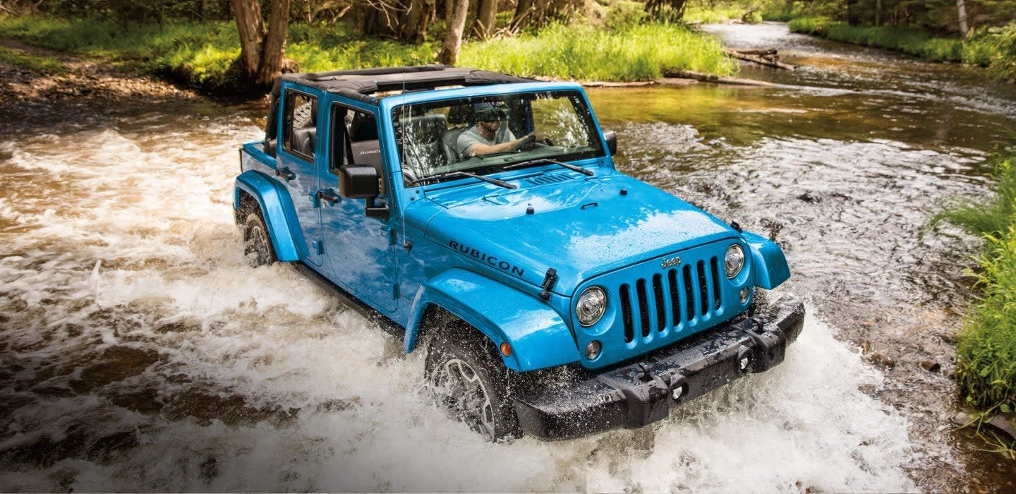 Blue Chrysler jeep car in river