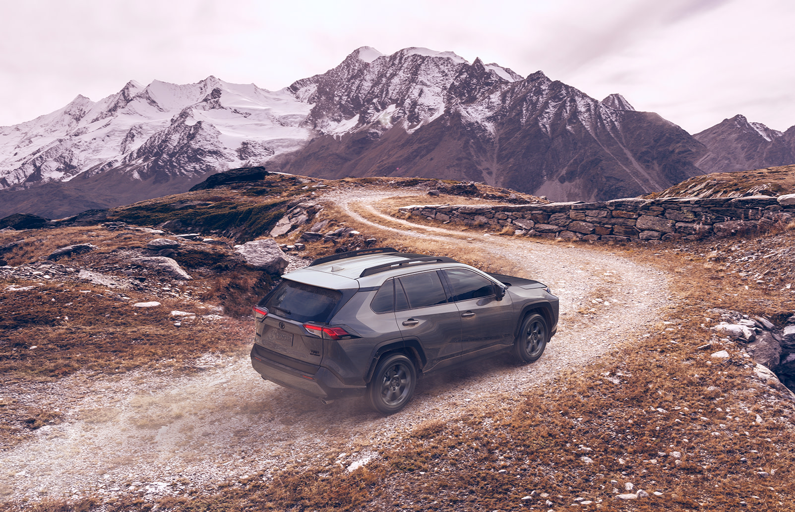 Compare the 2020 Toyota RAV4 vs. the Honda CR-V crossovers at Tri County Toyota | grey 2020 rav4 driving up the hill